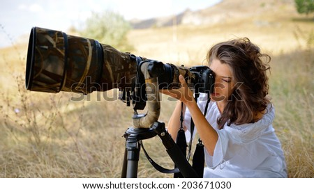 professional woman photographer on the field in summer - stock photo