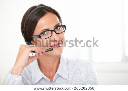 Professional woman with glasses conversing on her headphones while smiling and looking at you - copyspace