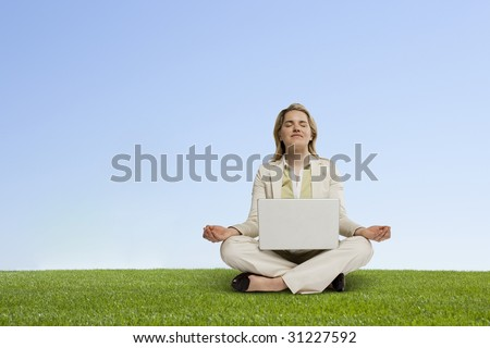 professional woman with laptop seated in zen position on grass - stock photo