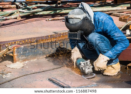 professional worker in construction industry grinding metal on a steel floor - stock photo