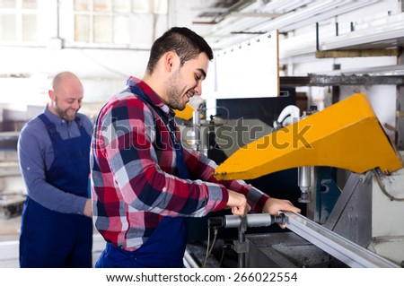 Professional workers producing windows on a factory. Cutting aluminum frames on a lathe - stock photo