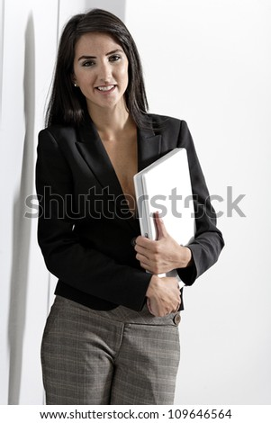 Professional working woman in corporate business suit holding a laptop computer - stock photo