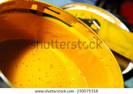Professional yellow paint in the opening of a special bucket - stock photo