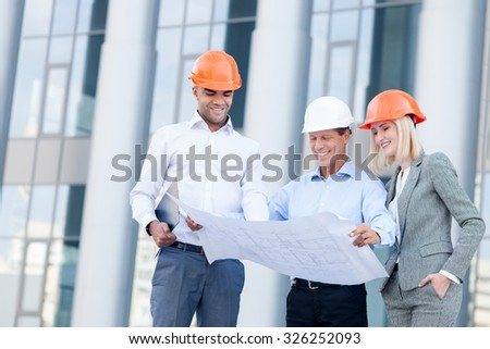 Professional young architects are discussing plan of building. They are wearing helmets and smiling. The foreman is standing and holding blueprint. The woman and man are looking there with interest