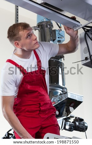 Professional young mechanic repairing factory machine, vertical