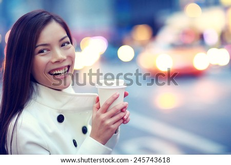 Professional young urban casual business woman happy in New York City Manhattan drinking coffee walking in street wearing coat downtown with yellow taxi cabs in background. - stock photo