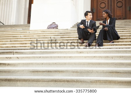 Professionally dressed man and woman sitting on an outdoor staircase having a conversation.