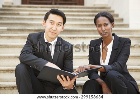 Professionally dressed man and woman sitting on an outdoor staircase make eye contact with the viewer.