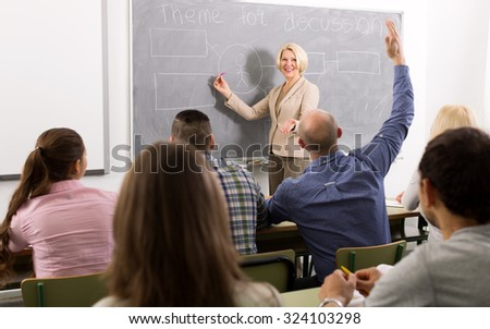 Professionals and cheerful adult female coach at training session for employees