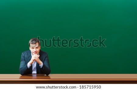 professor against chalkboard background - stock photo