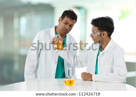 Professor and student or Scientific researchers looking at a liquid solution. - stock photo