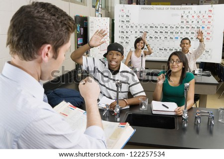 Professor asking question while students raising hands in classroom - stock photo