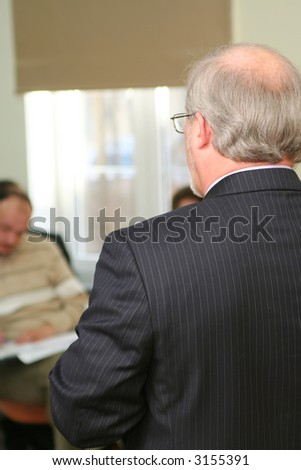 Professor before a students at seminar. View from back. - stock photo