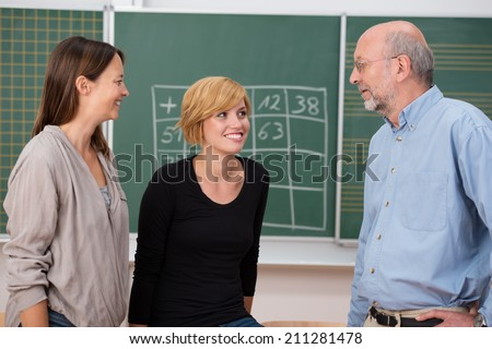 Professor in class with two university students standing chatting in front of the blackboard with two attractive young women - stock photo