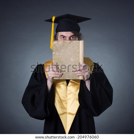 Professor in the academic dress with big old book in her hands. - stock photo
