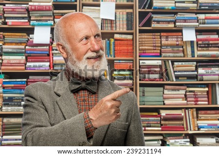 Professor iProfessor in the library of books on the background pointing at themn the library of books on the background pointing at them - stock photo