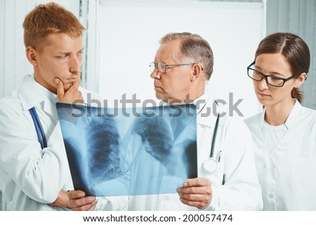 Professor older man doctor and young doctors examine x-ray image of lungs in a hospital - stock photo