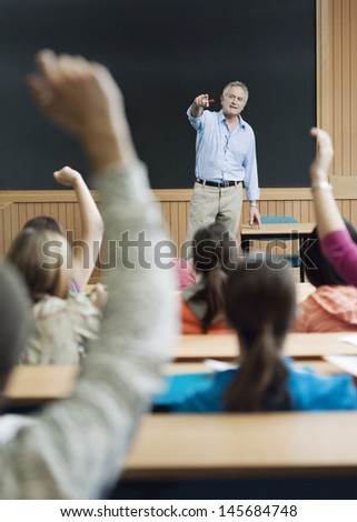 Professor picking out student for an answer in lecture room - stock photo