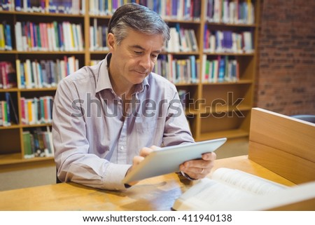 Professor sitting at desk using digital tablet in college library - stock photo
