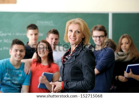 Professor standing in a classrom with a group of students in background - stock photo