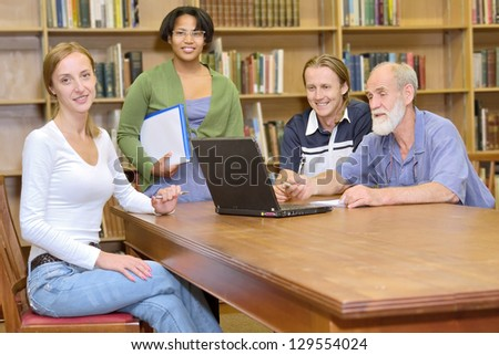 Professor with students - multiracial group of four friendly people studying in library. Shot in South Africa.