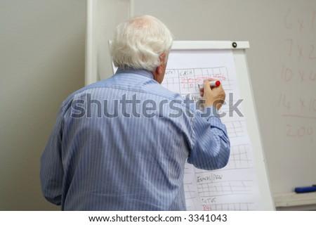 Professor writes on the blackboard in the MBA class - stock photo
