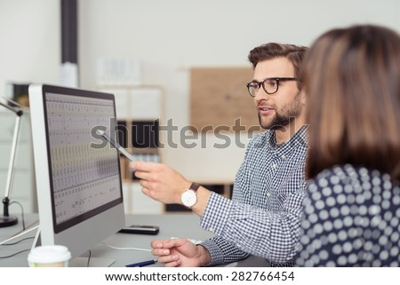 Proficient young male employee with eyeglasses and checkered shirt, explaining a business analysis displayed on the monitor of a desktop PC to his female colleague, in the interior of a modern office - stock photo