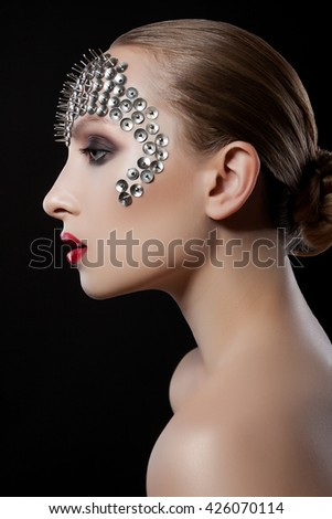 profile close-up portrait of a beautiful girl with spikes on his head on a black background