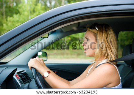 Profile face of fright woman sitting in the car and holds the wheel - outdoors - stock photo