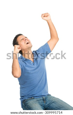 Profile good looking latino man wearing casual blue clothes sitting, looking up to heavens raising fists pumping, arms, celebrating achieving a goal or victory