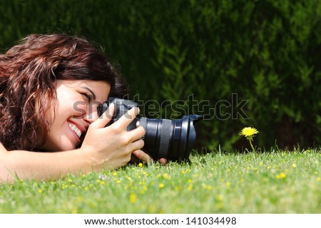 Profile of a beautiful woman taking a macro photography of a flower on the grass in a park - stock photo