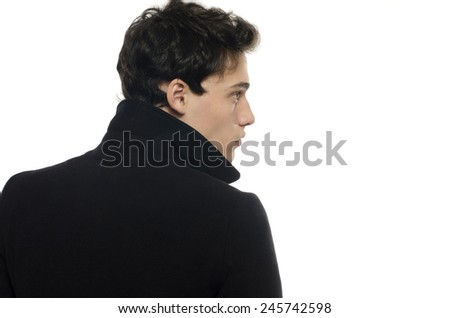 Profile of a beautiful young man dressed in a black long coat, posing fashion - stock photo