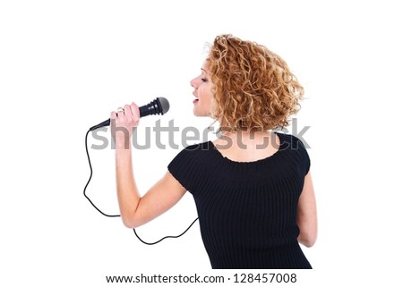 Profile of a beautiful young singer holding a microphone - studio shot - stock photo