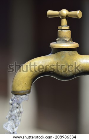 profile of a bronze metallic faucet with water drop - stock photo