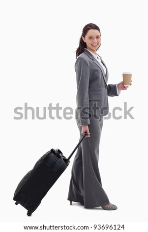 Profile of a businesswoman smiling with a suitcase and holding a coffee against white background