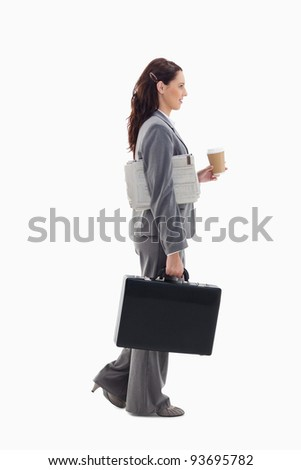 Profile of a businesswoman walking with a briefcase, with a newspaper under her arm and holding a coffee against white background - stock photo