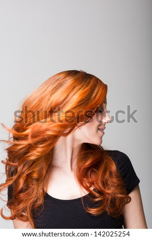 Profile of a cool redhead woman flicking her gorgeous long wavy hair so that it is flying loose around her face - stock photo