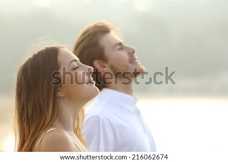 Profile of a couple of man and woman breathing deep fresh air together at sunset                - stock photo