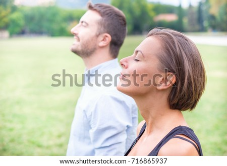 Profile of a couple of man and woman breathing deep fresh air together in the nature