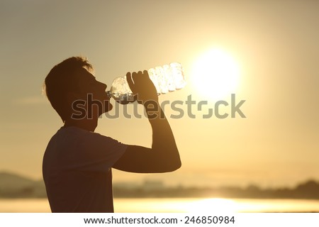 Profile of a fitness man silhouette drinking water from a bottle at sunset with the sun in the background - stock photo