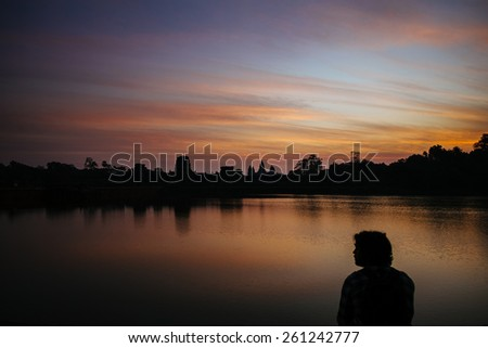 profile of a man against the backdrop of Angkor Wat at dawn