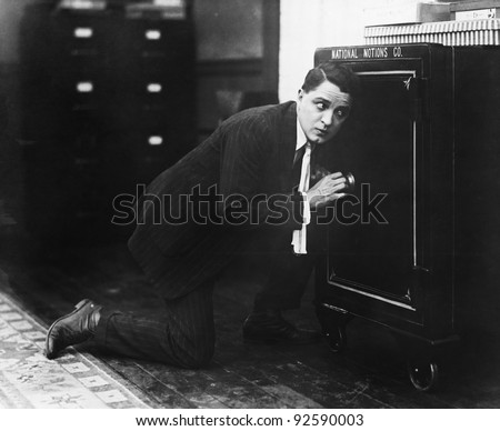 Profile of a man opening the door of a safe - stock photo