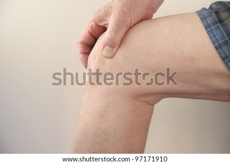 profile of a man's painful knee - stock photo