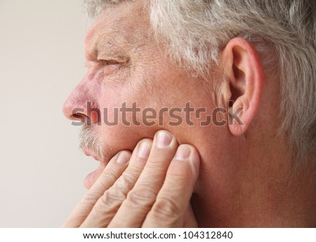 profile of a man suffering from pain in his jaw - stock photo