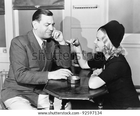 Profile of a man with a young woman smoking sitting in a cafe - stock photo