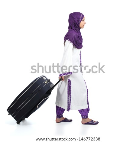 Profile of a muslim immigrant woman walking carrying a suitcase isolated on a white background                - stock photo