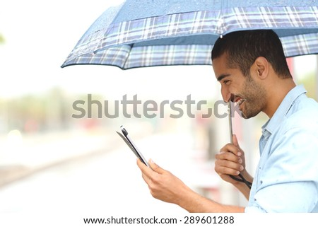 Profile of a muslim man reading a tablet under an umbrella in a rainy day - stock photo