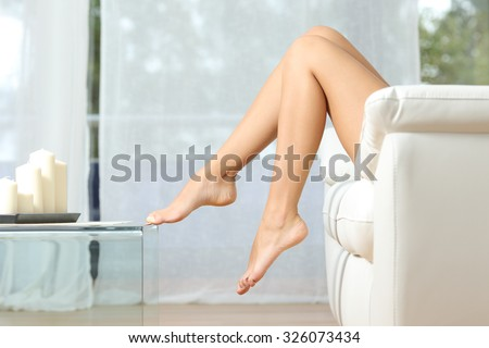Profile of a perfect woman legs sitting on a couch at home hair removal concept - stock photo