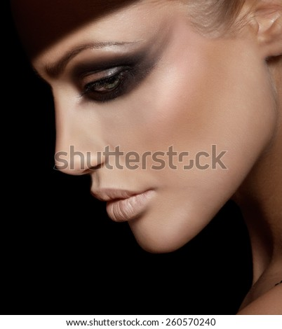 Profile of a sad woman with dark makeup. - stock photo