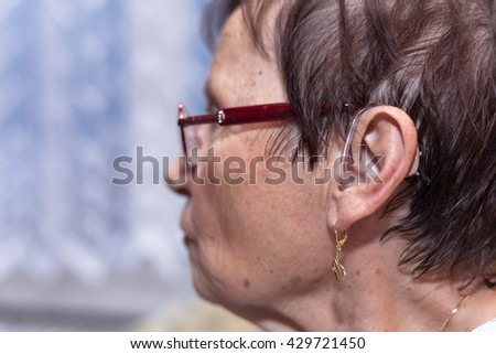 Profile of a senior woman with hearing aid. - stock photo